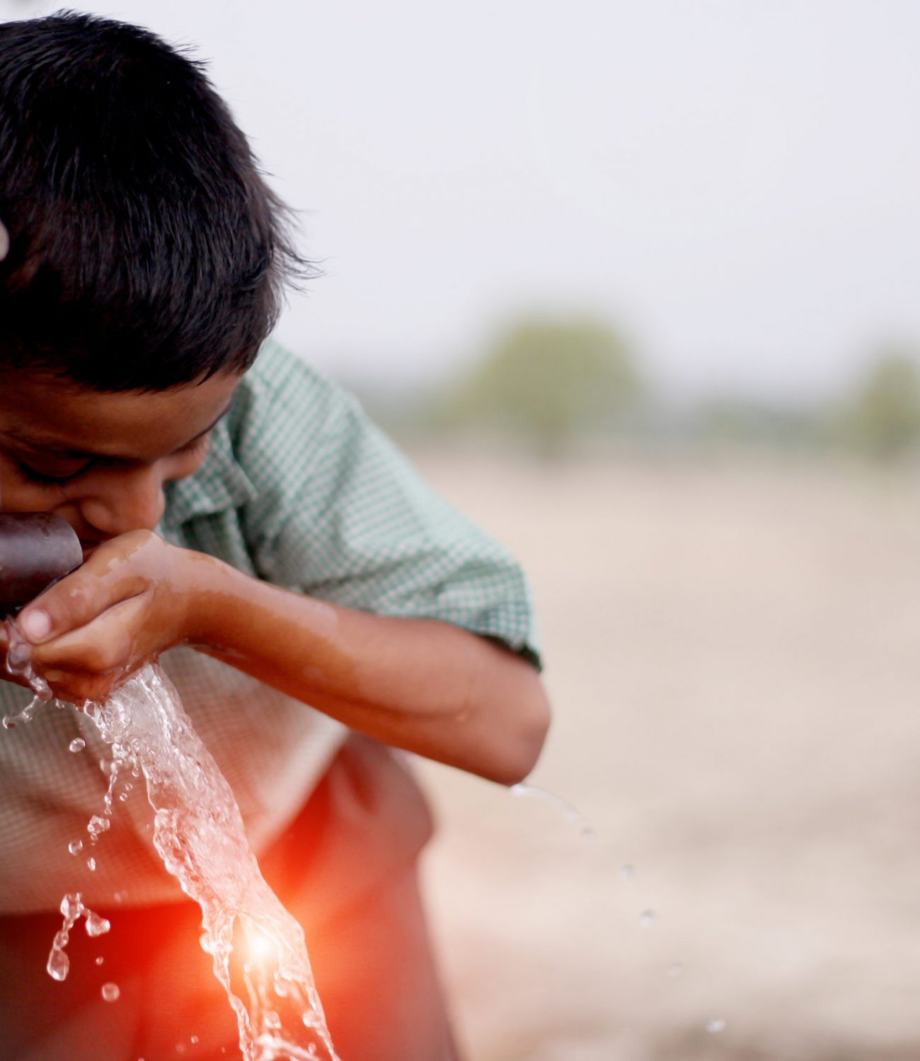 Thirsty child drinking water on water pump.